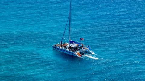 AX102_077.0000141F - Aerial stock photo of Catamaran with people in tropical blue water, Rada Fajardo, Puerto Rico