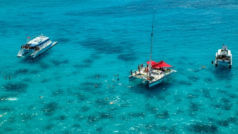AX102_078.0000040F - Aerial stock photo of Snorkelers and catamarans in tropical blue waters, Rada Fajardo, Puerto Rico