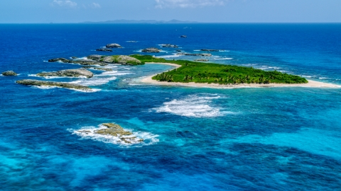 AX102_088.0000259F - Aerial stock photo of A green island surrounded by smaller rocky islands and tropical blue waters, Puerto Rico