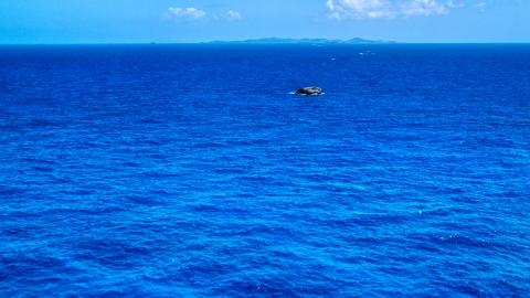 AX102_090.0000165F - Aerial stock photo of Tiny rocky island in sapphire blue ocean, Puerto Rico