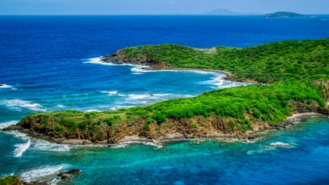 AX102_108.0000000F - Aerial stock photo of Rugged coastline of a tree covered Caribbean island in blue waters, Culebra, Puerto Rico