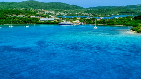 AX102_148.0000000F - Aerial stock photo of Ferry in the sapphire blue bay by a coastal town, Culebra, Puerto Rico