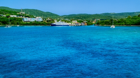 AX102_148.0000239F - Aerial stock photo of Ferry across a sapphire blue bay in Culebra, Puerto Rico