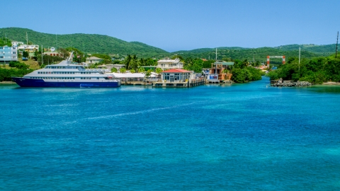 AX102_150.0000000F - Aerial stock photo of Ferry docked in sapphire waters by a waterfront town, and Culebra, Puerto Rico