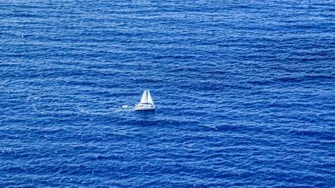 AX102_193.0000158F - Aerial stock photo of Catamaran sailing sapphire blue waters, Atlantic Ocean
