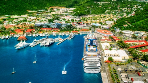 AX102_210.0000000F - Aerial stock photo of Cruise ship and yachts docked in sapphire waters at a Caribbean island town, Charlotte Amalie, St. Thomas