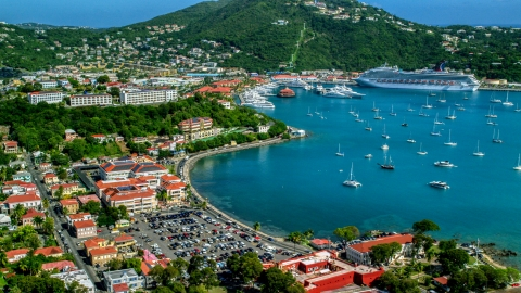 AX102_224.0000000F - Aerial stock photo of Sailboats and cruise ship in the harbor beside a Caribbean island town, Charlotte Amalie, St Thomas