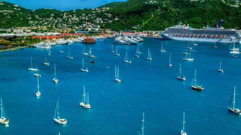 AX102_230.0000000F - Aerial stock photo of Sailboats and cruise ship in sapphire blue waters of the harbor in Charlotte Amalie, St Thomas