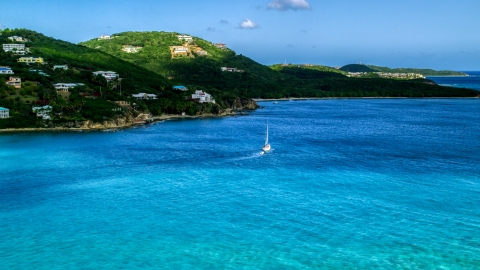 AX102_234.0000000F - Aerial stock photo of A sailboat near the Caribbean island coast with upscale homes, Southside, St Thomas