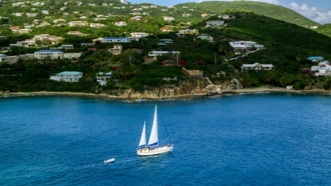 AX102_234.0000199F - Aerial stock photo of Sailboat near the island coast and oceanfront homes in Southside, St Thomas, the US Virgin Islands
