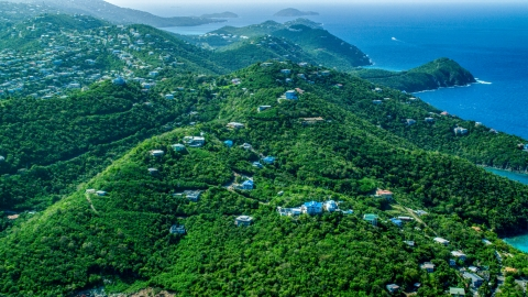 AX102_259.0000000F - Aerial stock photo of Hilltop island homes over looking the blue ocean waters by the coast, East End, St Thomas