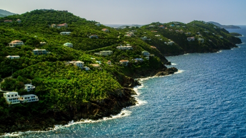 AX102_267.0000000F - Aerial stock photo of Hillside mansions on an island coast overlooking the ocean, Northside, St Thomas