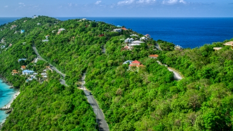 AX102_274.0000000F - Aerial stock photo of Oceanfront hillside homes with a view of turquoise Caribbean waters, Magens Bay, St Thomas