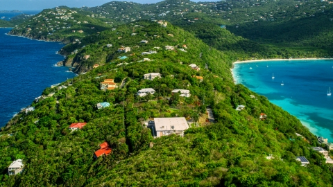 AX102_282.0000315F - Aerial stock photo of Oceanfront hillside island homes near sapphire blue Caribbean waters, Magens Bay, St Thomas