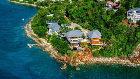 AX103_034.0000000F - Aerial stock photo of Oceanfront mansion beside turquoise blue Caribbean waters, Cruz Bay, St John