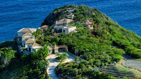 AX103_038.0000258F - Aerial stock photo of Hilltop mansion with a sapphire blue ocean view, Cruz Bay, St John