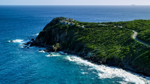AX103_043.0000356F - Aerial stock photo of Cliff top mansion among trees and sapphire blue Caribbean waters, Cruz Bay, St John