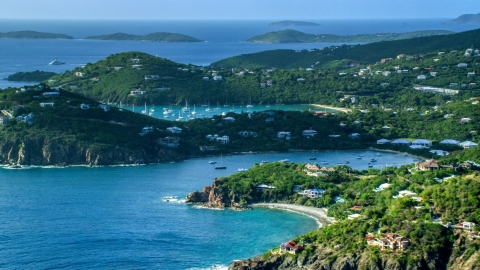 AX103_060.0000202F - Aerial stock photo of Hilltop and cliff top mansions along Caribbean blue waters, Cruz Bay, St John