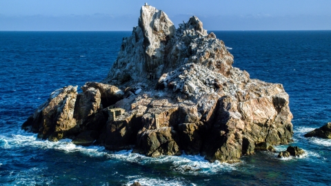 AX103_082.0000090F - Aerial stock photo of A jagged rock formation in Caribbean blue waters, St Thomas