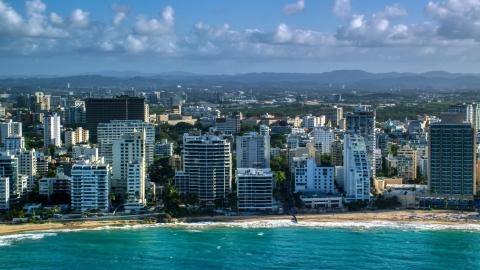 AX103_150.0000114F - Aerial stock photo of Beachfront condo complexes along Caribbean blue waters, San Juan, Puerto Rico