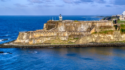 AX104_006.0000203F - Aerial stock photo of Iconic Fort San Felipe del Morro, Old San Juan, sunset