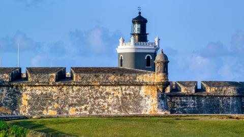AX104_023.0000000F - Aerial stock photo of Port San Juan Light and Fort San Felipe del Morro, Old San Juan, sunset