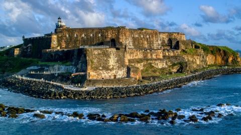 AX104_030.0000011F - Aerial stock photo of Fort San Felipe del Morro by calm ocean waters, Old San Juan, sunset