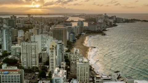 AX104_068.0000000F - Aerial stock photo of Beachfront hotels and ocean waters, San Juan, Puerto Rico, sunset