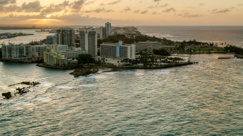 AX104_072.0000000F - Aerial stock photo of The oceanfront Caribe Hilton Hotel and Normandie Hotel, San Juan, Puerto Rico, sunset