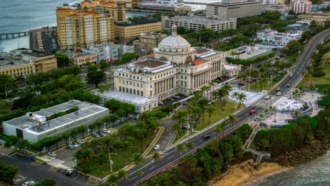 AX104_077.0000117F - Aerial stock photo of San Juan Capitol Building near the coast, Puerto Rico, sunset