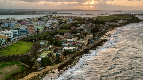 AX104_078.0000146F - Aerial stock photo of Oceanfront Caribbean homes, Old San Juan, Puerto Rico, sunset