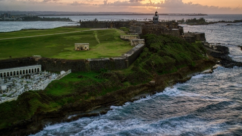 AX104_080.0000107F - Aerial stock photo of Fort San Felipe del Morro and lighthouse, Old San Juan, sunset