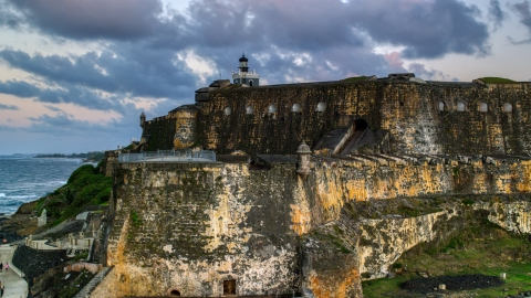 AX104_082.0000258F - Aerial stock photo of The walls of Fort San Felipe del Morro by Caribbean blue waters, Old San Juan, twilight