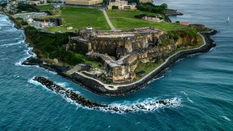 AX104_084.0000000F - Aerial stock photo of A view of Fort San Felipe del Morro along Caribbean blue waters, Old San Juan, twilight