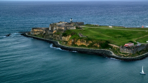AX104_086.0000000F - Aerial stock photo of Fort San Felipe del Morro surrounded by Caribbean blue ocean waters, Old San Juan, twilight