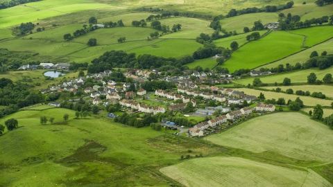 AX109_003.0000117F - Aerial stock photo of Rural homes surrounded by green fields, Banton, Scotland