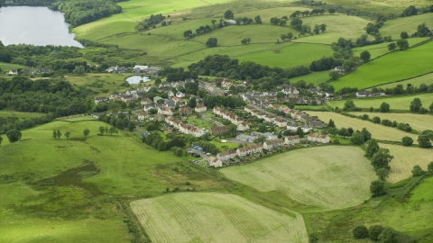 AX109_003.0000251F - Aerial stock photo of Rural homes surrounded by green fields in the village of Banton, Scotland