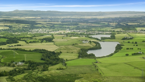 AX109_004.0000000F - Aerial stock photo of Green farm fields and a reservoir, Denny, Scotland