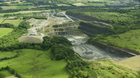 AX109_009.0000156F - Aerial stock photo of Farmland surrounding a quarry, Denny, Scotland