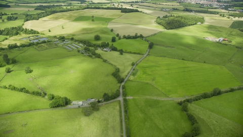 AX109_010.0000000F - Aerial stock photo of Farms and green farm fields in Stirling, Scotland