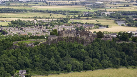 AX109_019.0000084F - Aerial stock photo of A view of hilltop Stirling Castle among trees, Scotland