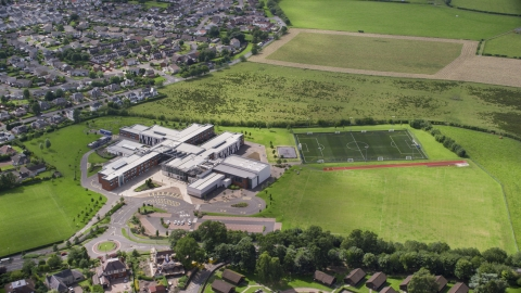 AX109_054.0000000F - Aerial stock photo of Wallace High School and soccer field, Stirling, Scotland