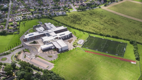 AX109_055.0000000F - Aerial stock photo of A view of Wallace High School and soccer field, Stirling, Scotland