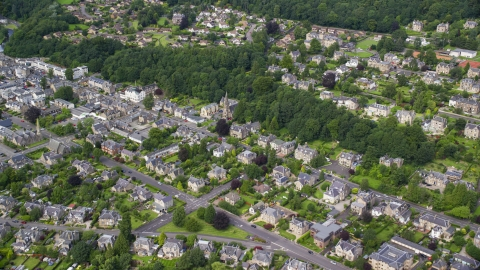 AX109_057.0000000F - Aerial stock photo of A residential neighborhood with church and trees, Stirling, Scotland