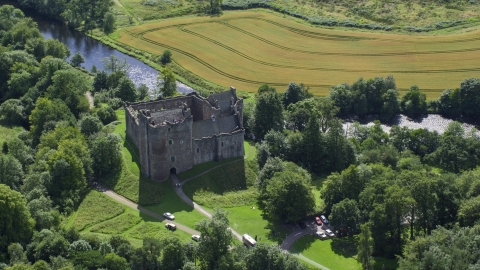 AX109_067.0000164F - Aerial stock photo of Riverfront Doune Castle with trees, Scotland
