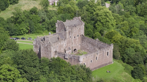 AX109_071.0000000F - Aerial stock photo of Doune Castle with tourists on the grounds, Scotland