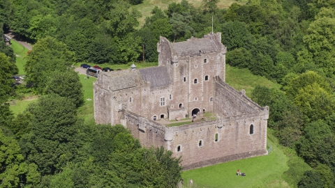 AX109_071.0000116F - Aerial stock photo of Historic Doune Castle with tourists on the grounds, Scotland