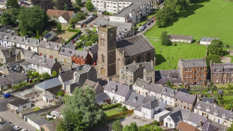 AX109_073.0000000F - Aerial stock photo of A church in a residential area, Doune Scotland