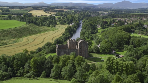 AX109_076.0000000F - Aerial stock photo of Doune Castle and River Teith lined with trees, Scotland