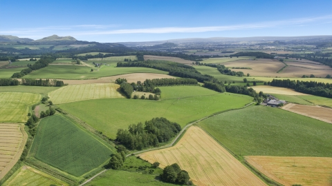AX109_089.0000000F - Aerial stock photo of Farm and fields along a country road, Doune, Scotland